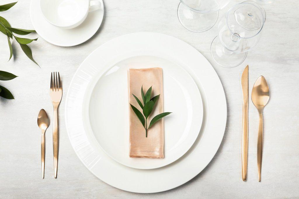 Zastawa obiadowa na stole: białe talerze i złote sztućce